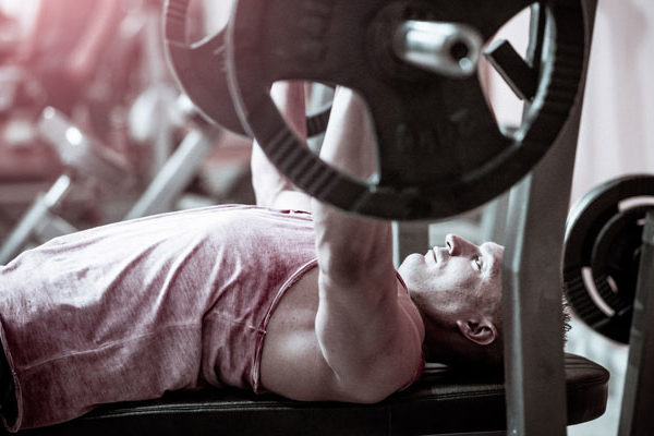 Male performing bench press